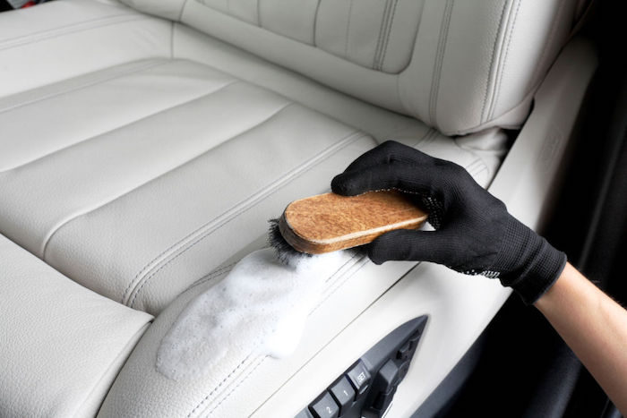 cleaning the leather seats of a vehicle with a special paste and a soft brush