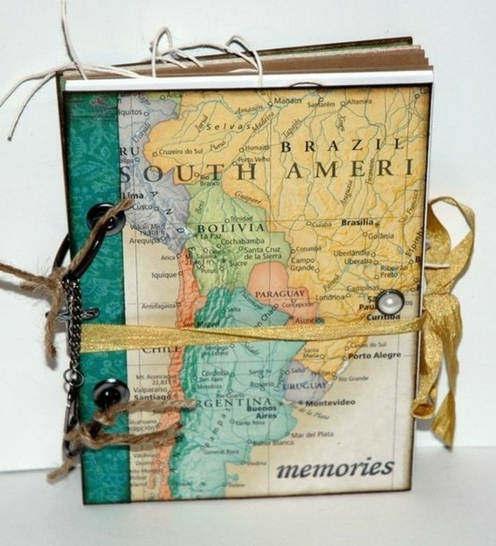 adventure journal, notebook, colorful map stuck on cover, golden ribbon, pearl sicker, rope and chain details, light background