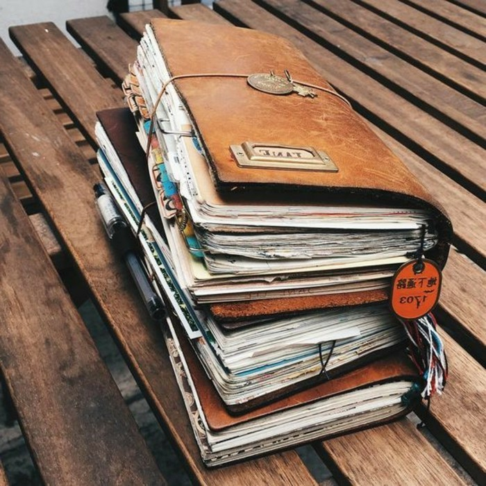 adventure journal, three big journals in light brown, with many colorful pages, stacked on top of each other, each tied with string, on a bench