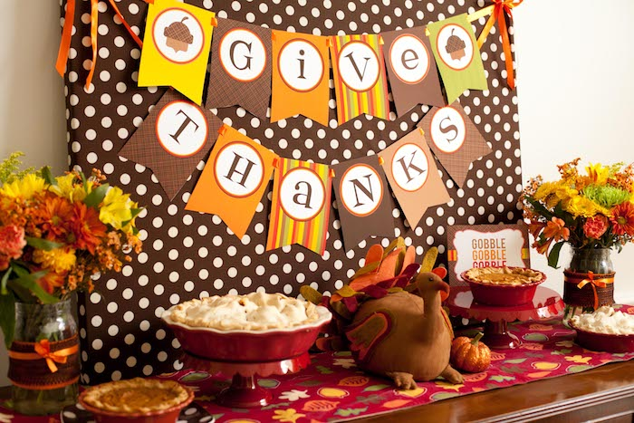 brown board with white polka dots, with a banner in yellow, orange, brown and green, spelling give thanks, near a wooden table with an autumn-leaf-patterned tablecloth, containing four pies in red dishes, a stuffed toy turkey, two decorated jars with yellow, orange and red flowers and a small pumpkin