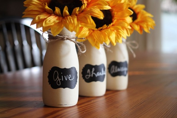beautiful thanksgiving pictures, three bottles, painted white, with black labels reading give, thanks, always, tied with string, containing three sunflowers, placed on a wooden table with a chair in the background