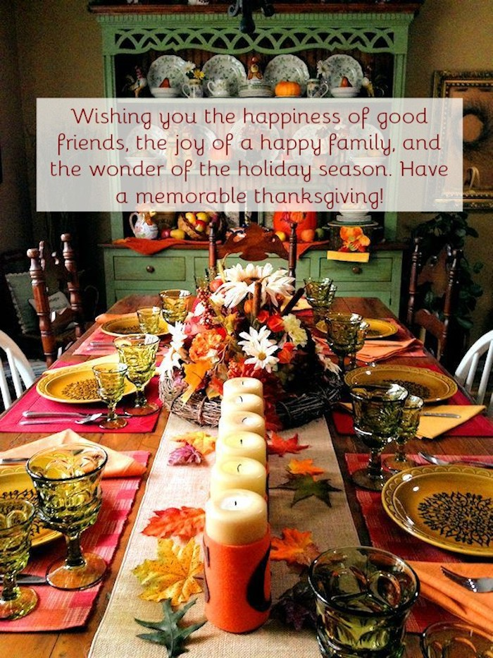 beautiful thanksgiving pictures, wooden table set up for thanksgiving, linen tablecloth, yellow decorated plates, green wine and water glasses, cutlery, white candles in orange candle holders, yellow, orange, red and green autumn leaves decorations, center piece containing flowers, yellow and orange napkins, white and brown chairs, green cabinet with crockery in the background, festive message