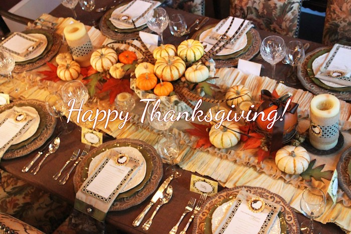 brown wooden table with brown plates, napkins and white menus, silver cutlery, yellow tablecloth, decorated with red autumn leaves, small yellow and orange pumpkins, two candles, pheasant feathers, crystal wine and water glasses, name cards