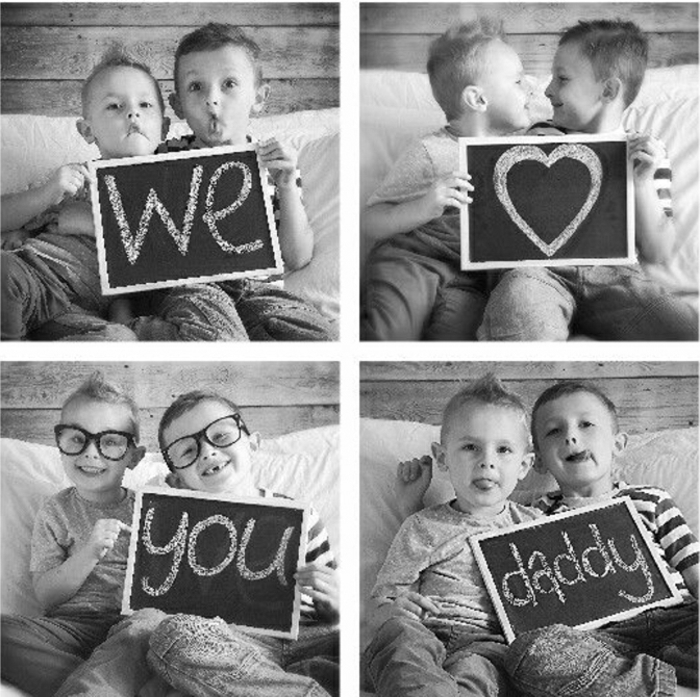 "two little boys sitting on a white couch, holding a sign which reads ""we heart you daddy"", black and white photos, funny glasses"