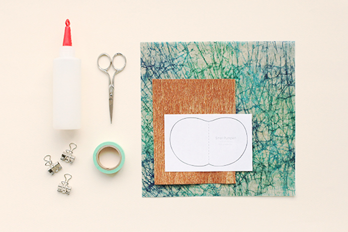 blue and orange specked pieces of craft paper, a white print out, a roll of masking tape, metal scissors, bottle of glue with red cap, three binder clips, on a cream background