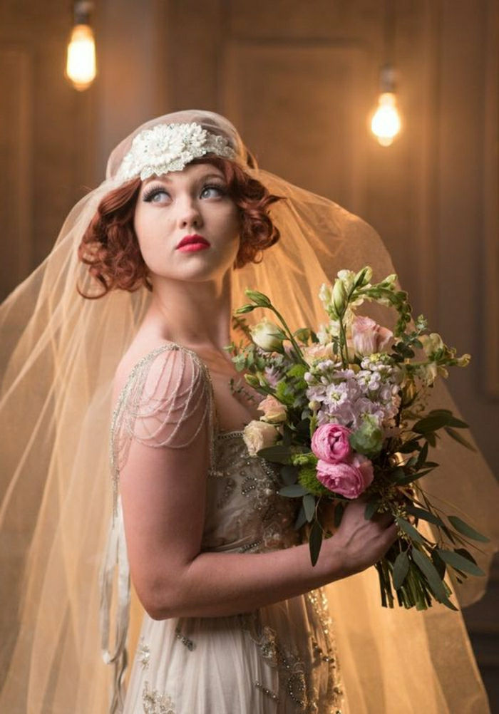 vintage inspired wedding dresses, woman with red lipstick and hair looking up, wearing vintage 1920s headdress and fail and bridal gown with lace beads and pearls, holding a large bouquet of differently colored flowers