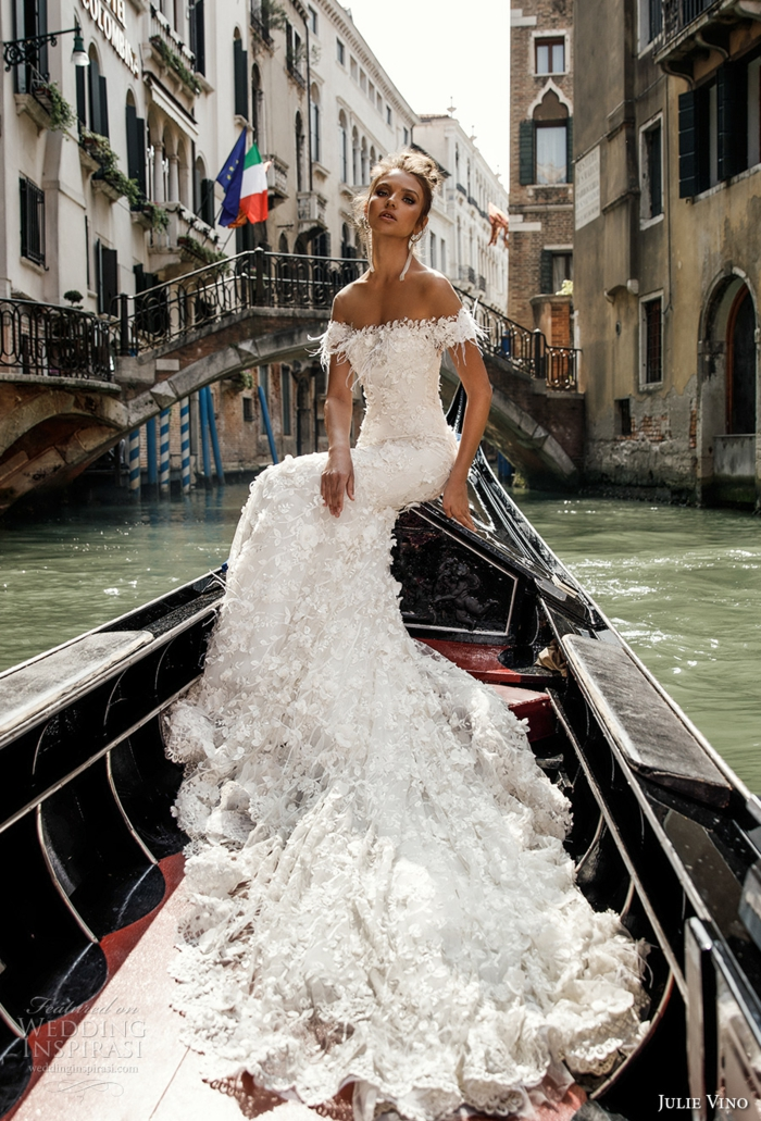 vintage wedding dresses, young brunette woman sitting on a gondola, sailing on a canal in venice, wearing long white frilly wedding dress with lace and embroidery