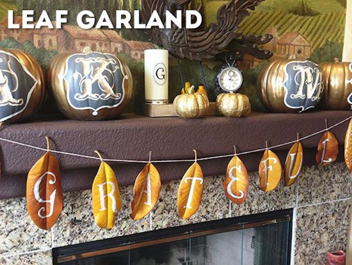 a garland made of yellow and orange autumn leaves spelling out grateful with white fancy letters,tied to a brown mantle containing four carved gold and blue pumpkins, two small golden pumpkins, a watch, a candle and a large painting, over a fireplace