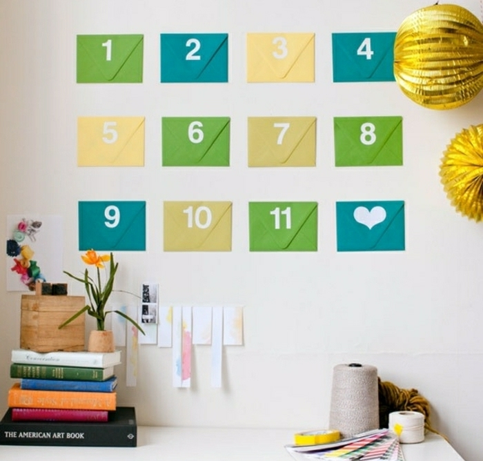 green, blue and yellow numbered envelopes, stuck to a white wall, near decorative ornaments, books and craft supplies