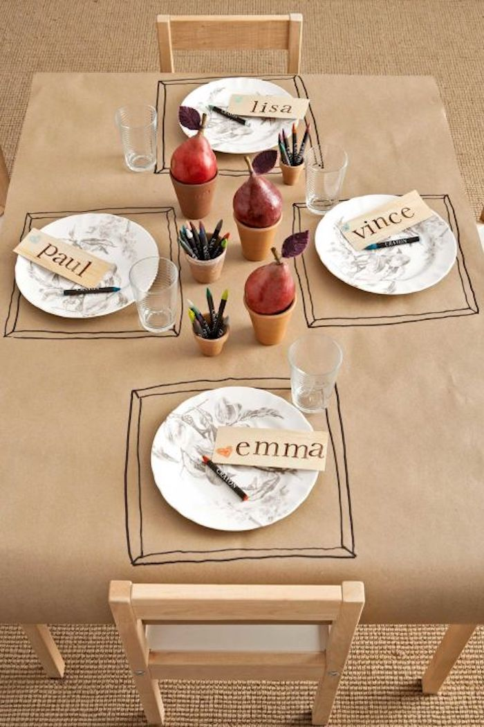 cute happy thanksgiving images, a paper tablecloth in sepia with table mats drawn by kids, four plates with name tags, three cups with crayons, four glasses, three cups holding red pears, two chairs