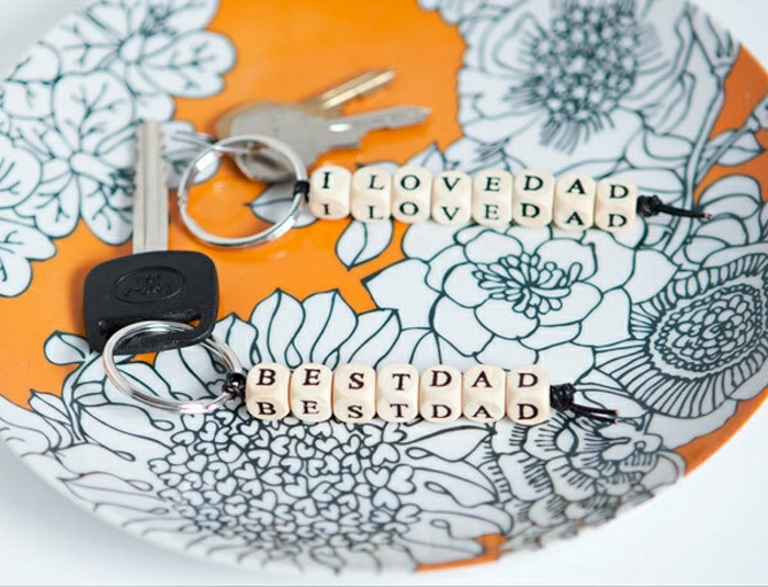 "diy father's day gift ideas finished keychains attached to keys, with alphabet beads spelling ""I love dad"" and ""best dad"", placed on a yellow plate with white flowers"