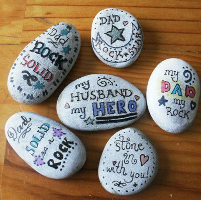 diy father's day gift ideas, 6 grey stones placed on a wooden table, with messages written in marker