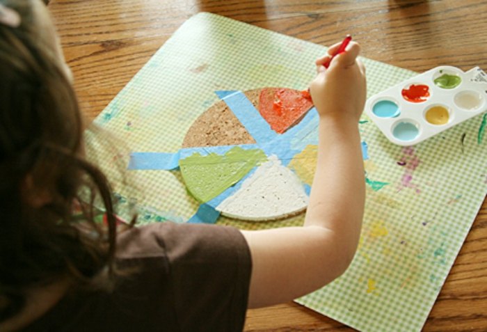 dyi gift ideas, a child painting a cork coaster placed on a working green and white mat in different colors, a palette with blue, red, yellow, white and green paint placed on a wooden table