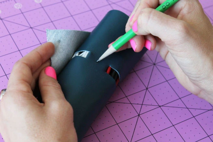 father's day craft ideas, a female hand with pink nail polish, marking the place of the button on the faux leather with a green pencil, pink cutting mat in the background