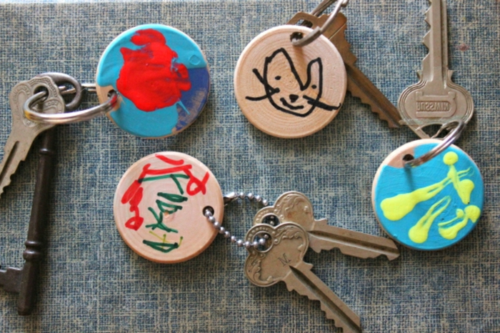 father's day craft ideas, wooden keychains painted by children, attached to vintage keys, on a dark blue and cream background