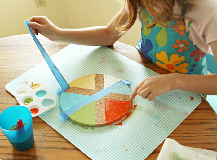father's day diy gifts, a child removing masking tape from the cork coaster she has painted with red, yellow, green, white and blue colors