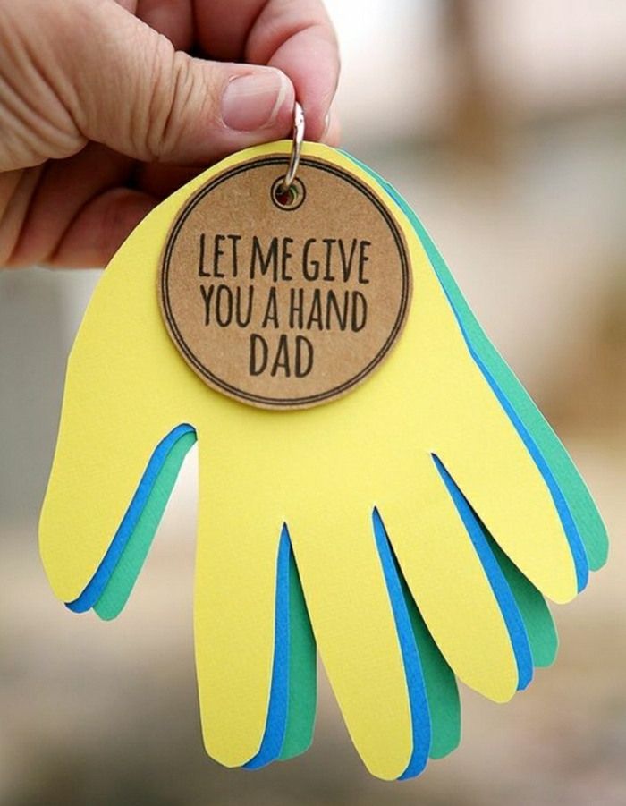 paper cutouts of a child's hand in yellow, blue and green, held by a keychain, with a light brown label, held by a man's hand