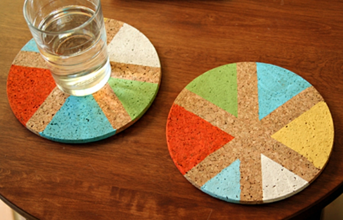 father's day diy gifts, cork coasters painted with red, blue, green, white and yellow colours placed on a brown wooden table, a glass of water is placed on one of them