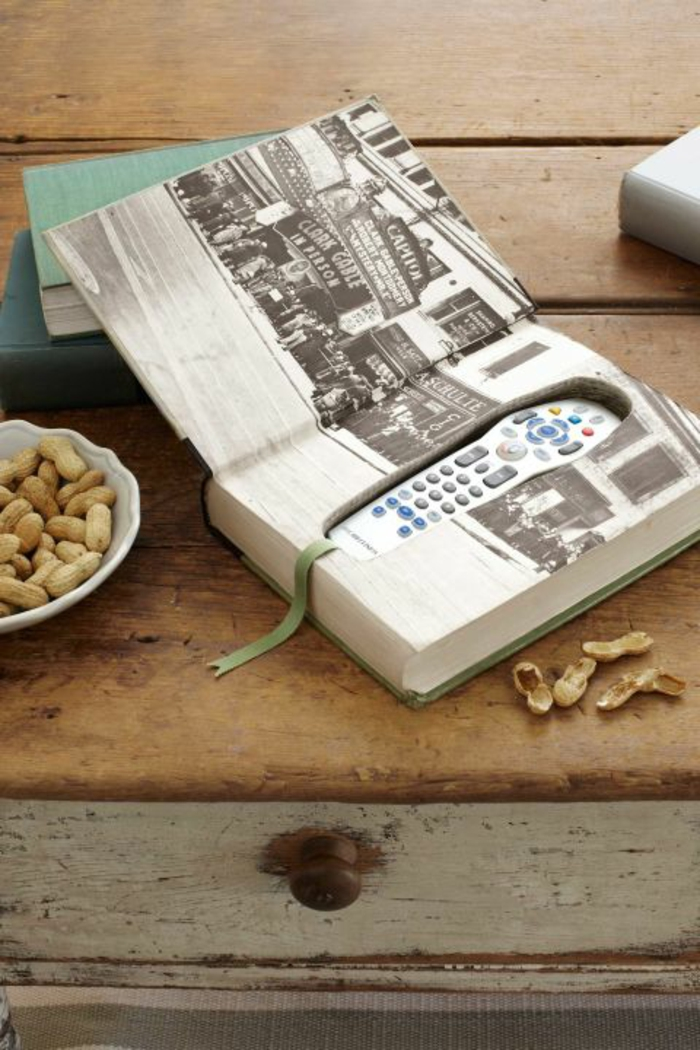father's day diy gifts, a book with a hidden compartment containing a remote control, placed on a wooden table, near a bowl of peanuts and other books