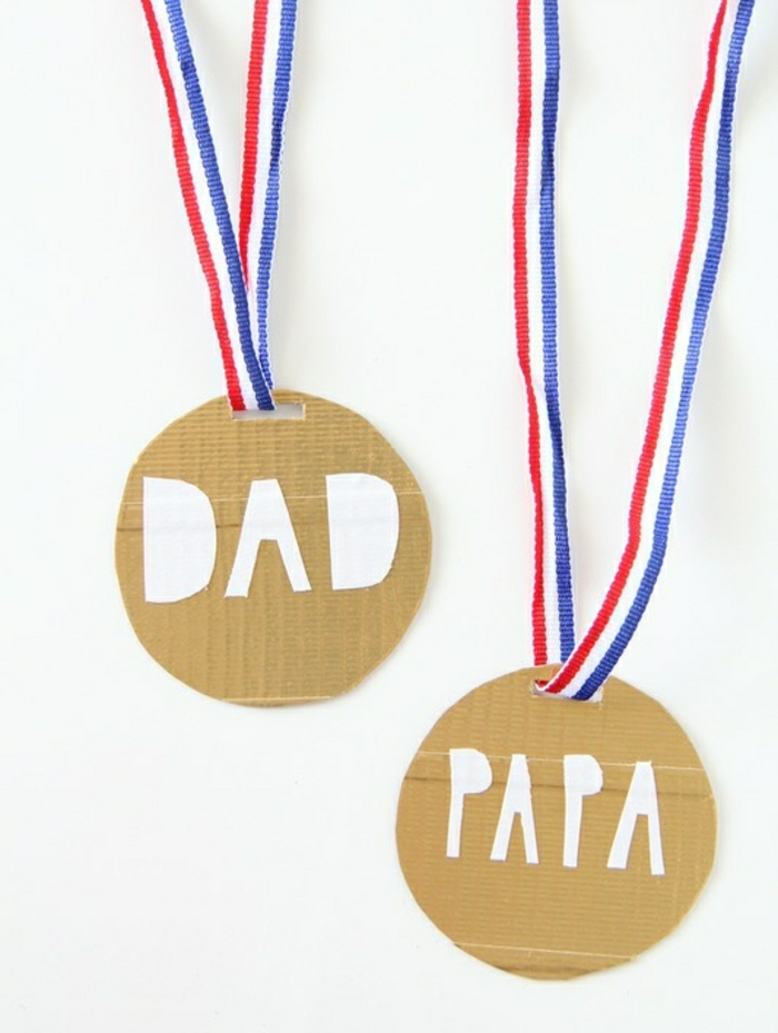 "father's day gifts from daughter, two medals made from yellow cardboard, with red, white and blue ribbons and the words ""dad"" and ""papa"" stuck on them, on a white background"