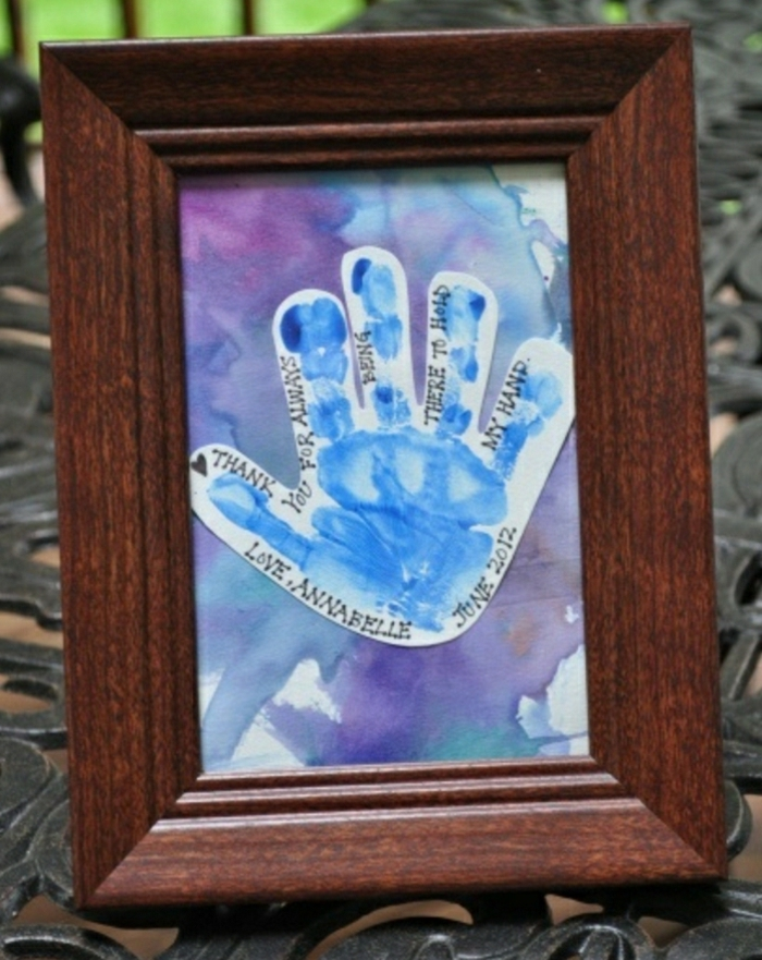 father's day gifts from daughter, a blue cutout of a child's hand, painted in blue and violet, in a dark wooden frame
