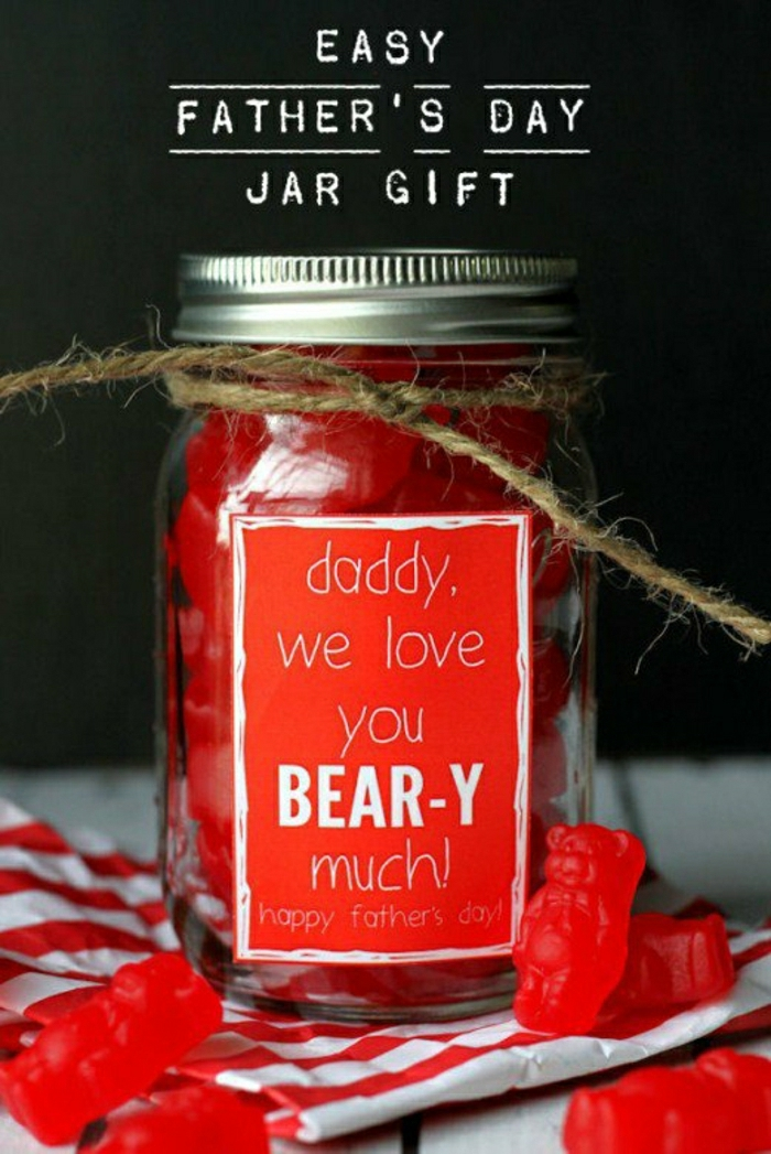 father's day gifts from daughter, mason jar with screw cap, tied with string, filled with red gummy bears, with a red label on a table, next to more red gummy bears