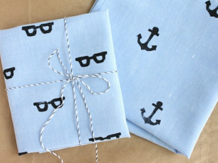 father's day homemade gifts, completed hand printed light blue fabric, featuring black glasses and anchor motives, tied with a striped string, on a light brown background