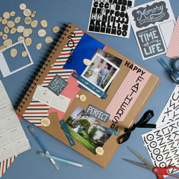 father's day homemade gifts scrapbook, collage photo album with stickers, photos, pens and scissors on a blue table