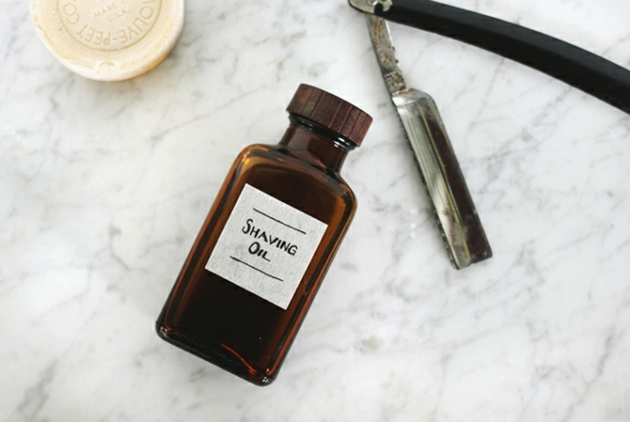 father's day homemade gifts, homemade shaving oil in a dark brown bottle placed on a marble table, next to a round bar of soap and an old-fashioned razor