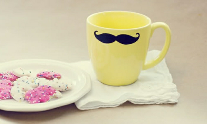 father's day homemade gifts, yellow mug with black moustache, placed on a white napkin, near a white plate with pink and white cookies, pale background