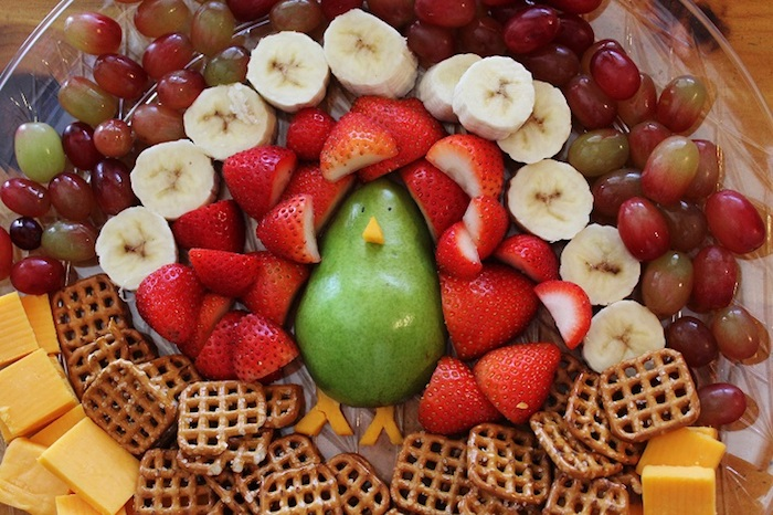 funny happy thanksgiving images, a pear, strawberry and banana slices, grapes, cheese slices and salted biscuits made to look like a turkey, placed on a clear plate, sitting on a wooden table