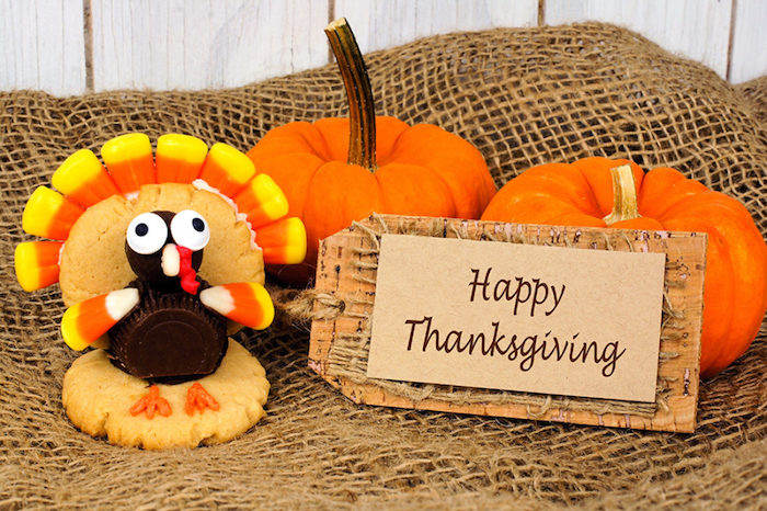 funny happy thanksgiving pictures, a turkey made from cookies, chocolates and candy-corn, attached to a label saying happy thanksgiving, near two pumpkins, on a burlap and white wood background