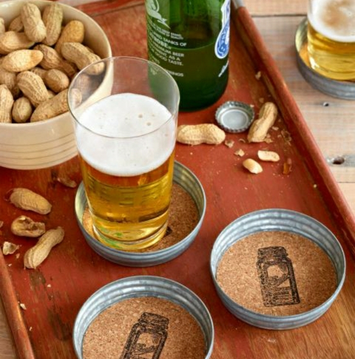 hand made bear coasters, on a brown tray, with a glass and a bottle of beer and a dish of peanuts, on a wooden table