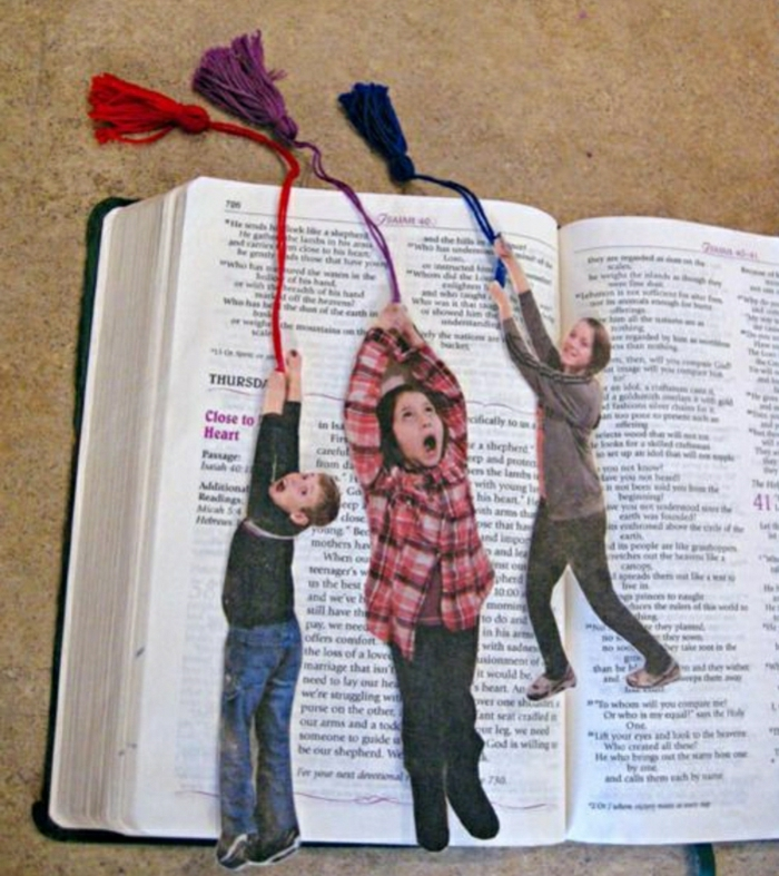 cute handmade bookmarks, made from kids' photos, holding colorful pieces of string, placed on a book, light brown background