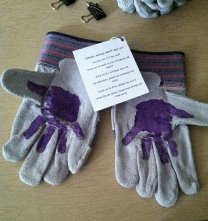grey working gloves with child's hadnprints in violet, on a light brown wooden table
