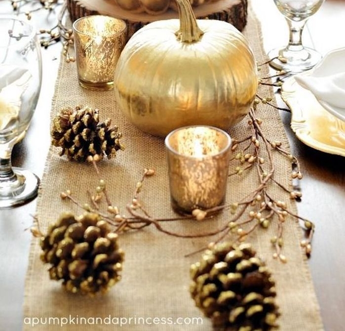 happy thanksgiving pictures, a table with burlap tablecloth, gold-painted pumpkins, candle-holders, pine-cones and branches, white and yellow plates, clear glasses, light background