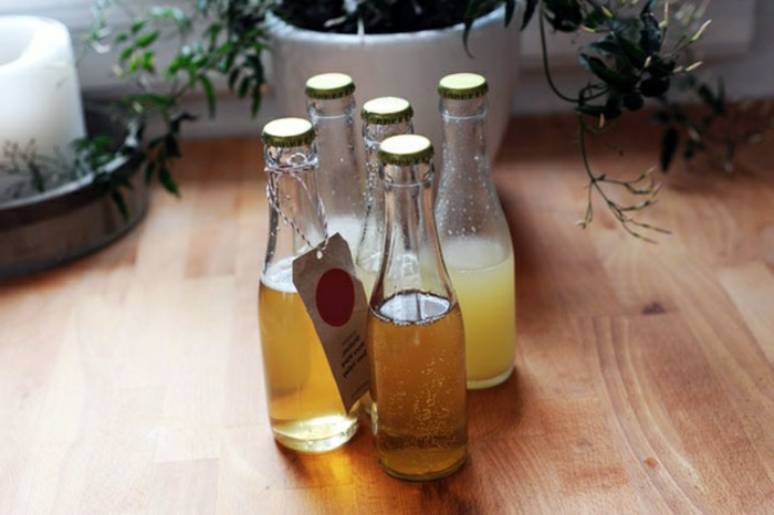 yellow homemade cocktails, clear glass bottles, with a label, on a wooden floor with flower pots in the background