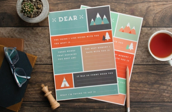 homemade father's day cards, green-blue, orange, dark blue and white, with mountains, trees and tents, on a dark wooden table, near glasses, books, s chess piece, a pencil, a potted plant and a cup of tea