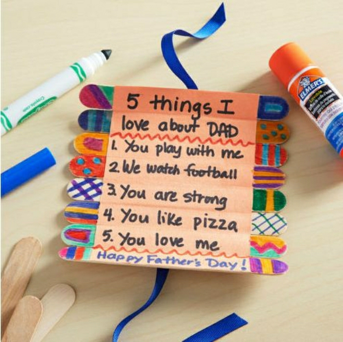 homemade father's-day cards, wooden ice cream sticks stuck together and painted with markers, dark blue ribbon, a stick of glue, a green marker, pale background