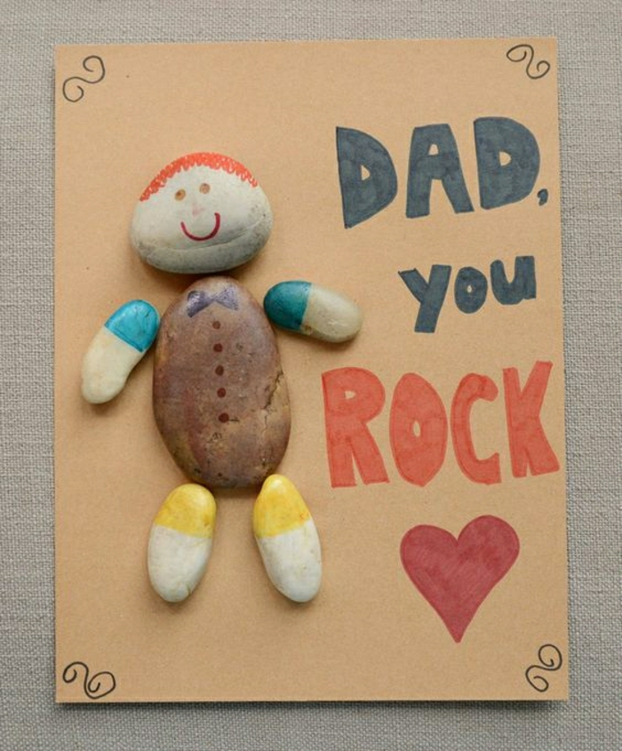 "homemade father's day cards, orange cardboard with painted pebbles in the shape of a boy stuck to it, with the words ""dad, you rock"" written in marker"