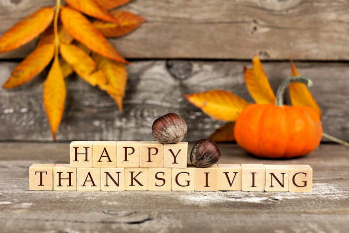 images of thanksgiving, light wooden blocks spelling happy thanksgiving in dark brown writing, decorated with two chestnuts, on a background featuring planks, orange autumn leaves and a pumpkin