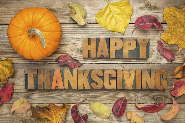 images of thanksgiving, happy thanksgiving woodcarving, on a background with wooden planks, red, orange, brown and yellow leaves and an orange pumpkin