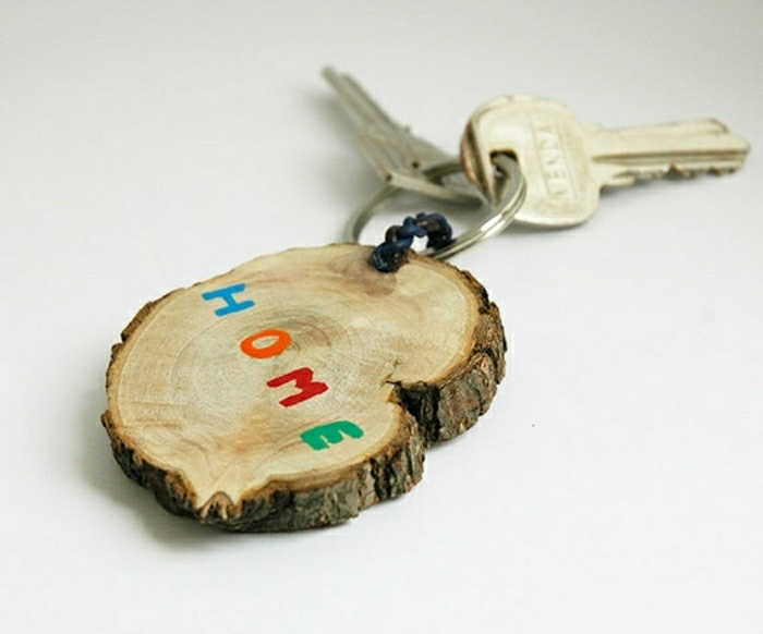 "keychain made from a piece of wood, with the words ""home"" painted on it in blue, orange, red and green, with a key attached, on a white background"