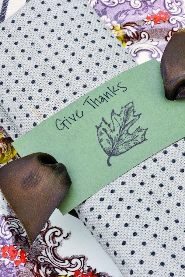 napkin made of light blue fabric with dark blue polka dots, with a brown ribbon and a green label with a stamp and the writing give thanks, on a colorful tablecloth