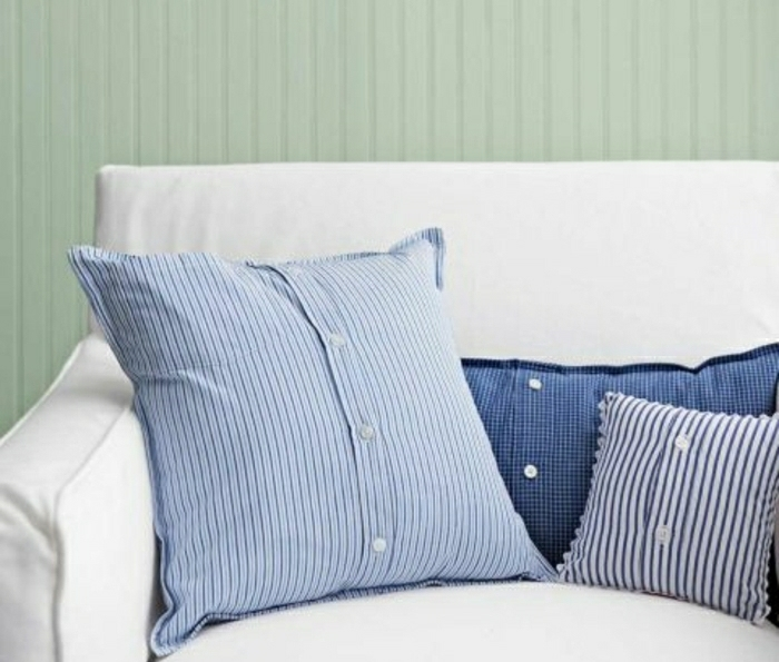 striped pillow covers made from old shirts, in different tones of blue, with white buttons, on a white sofa with light green background