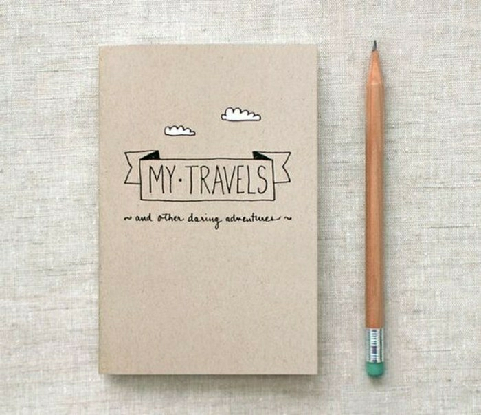 scrapbook page ideas, cardboard cover notebook, recycled paper, drawings of a banner and clouds, pencil, grey background