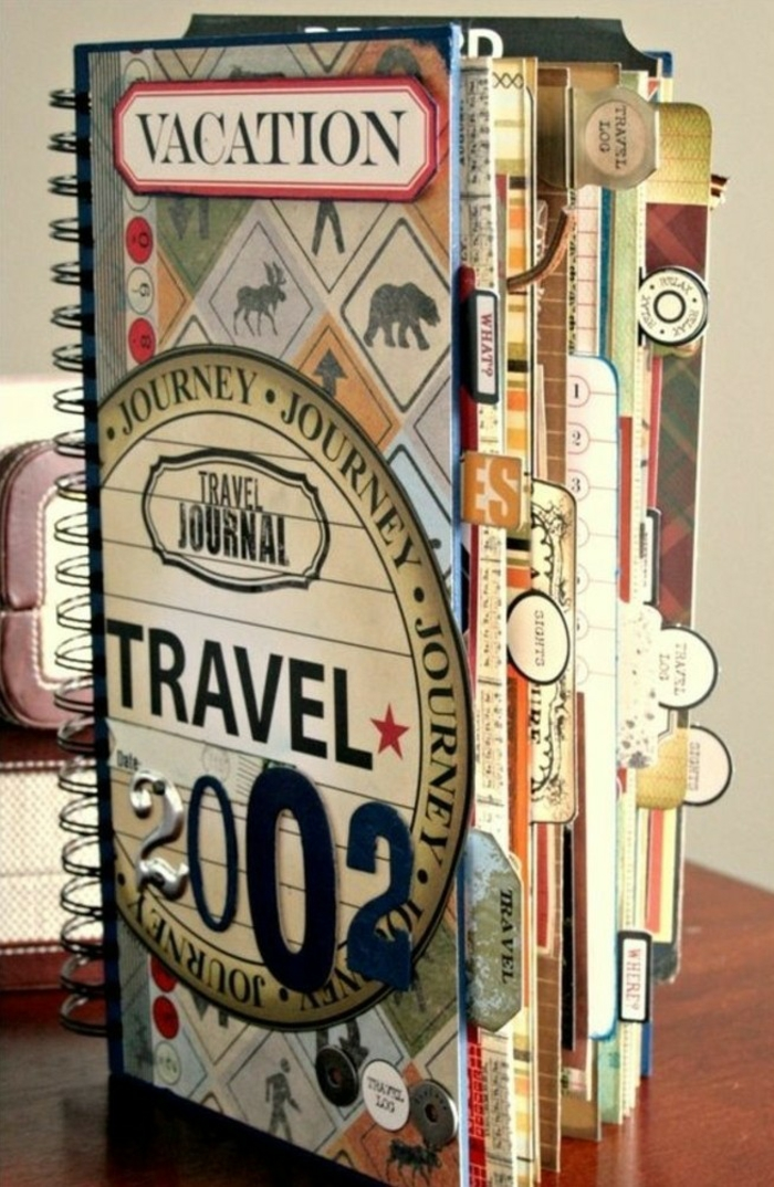 scrapbooking ideas, notebook with colorful pages and black binding, stickers, cutouts and a label saying vacation, on a wooden surface