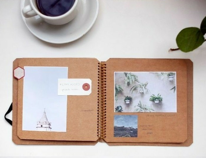 scrapbooking made simple, notebook made of brown recycled paper with three photos, on a white table with full coffee cup and green leaf