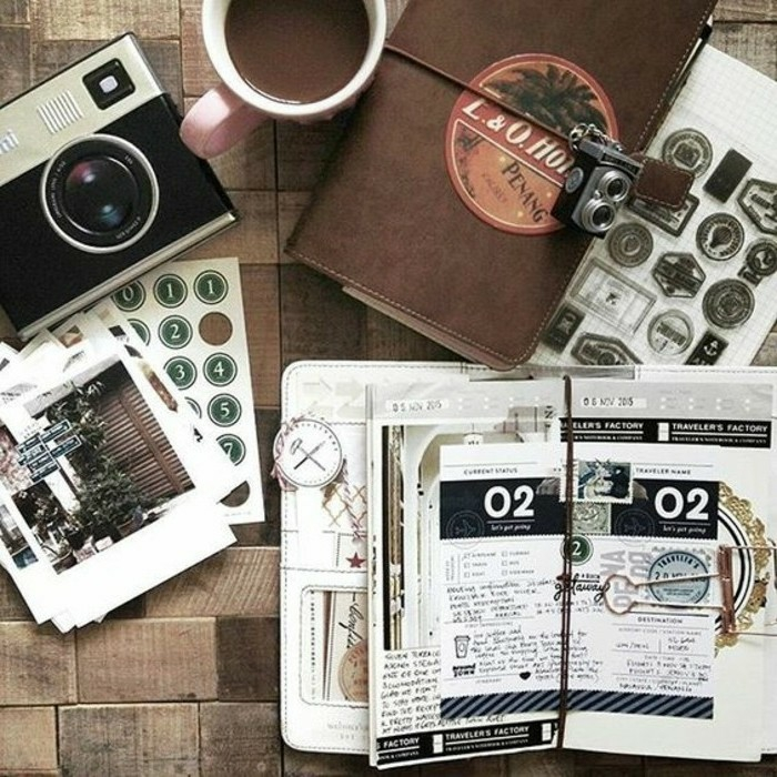 scrapbooking made simple, an old camera, two journals, one brown, closed, tied with string and lock, the other open, cutouts, stamps, stickers, photos