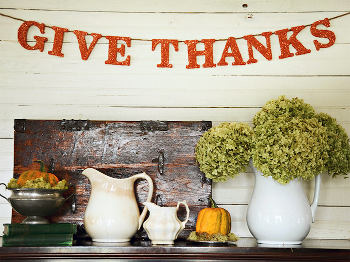 brown shelf containing a white vase with green flowers, a big white milk jug, a small white milk jug, a metal pot placed on two green books containing green moss and a small pumpkin, a small metal dish with a pumpkin, a wooden ornament, a wall made of light wooden planks with an orange glittery banner reading give thanks